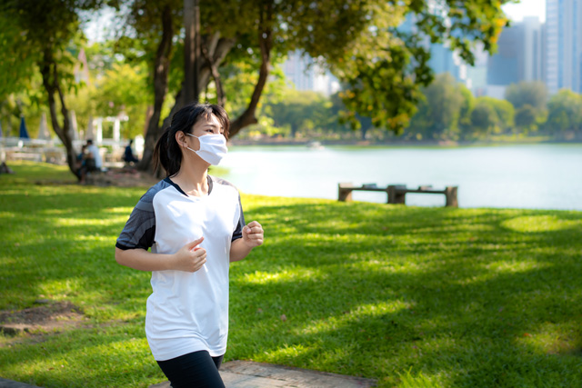 woman running in the park with a mask on